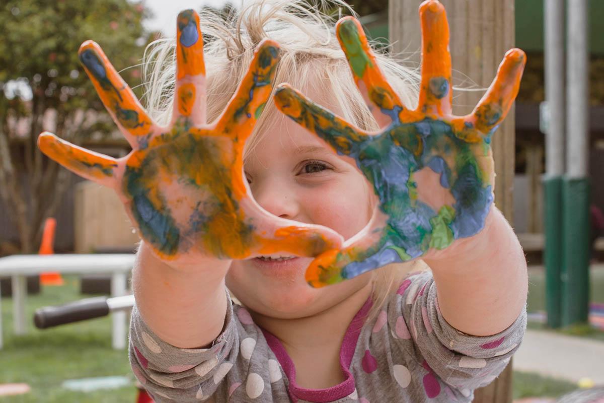 Lapsi leikkimässä sormiväreillä