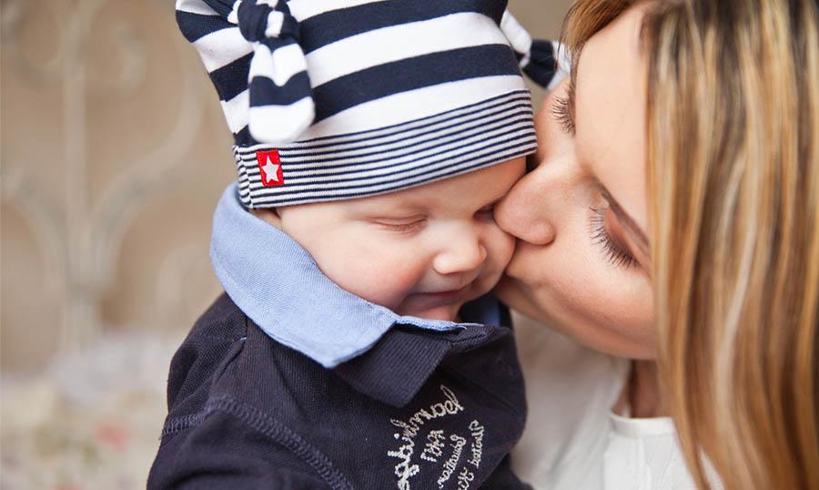 Äiti antamassa suukon lapsen poskelle
